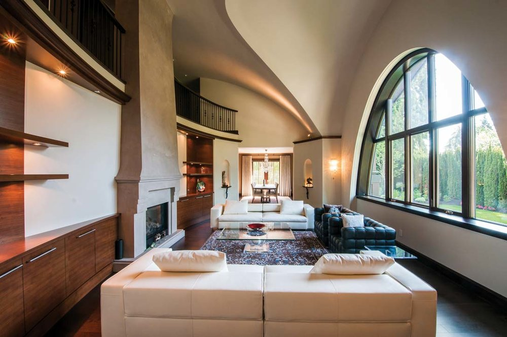 Curved lines of the vaulted ceiling are carried through to the millwork embracing the living-room fireplace. Oval window provides wide-angle garden views.