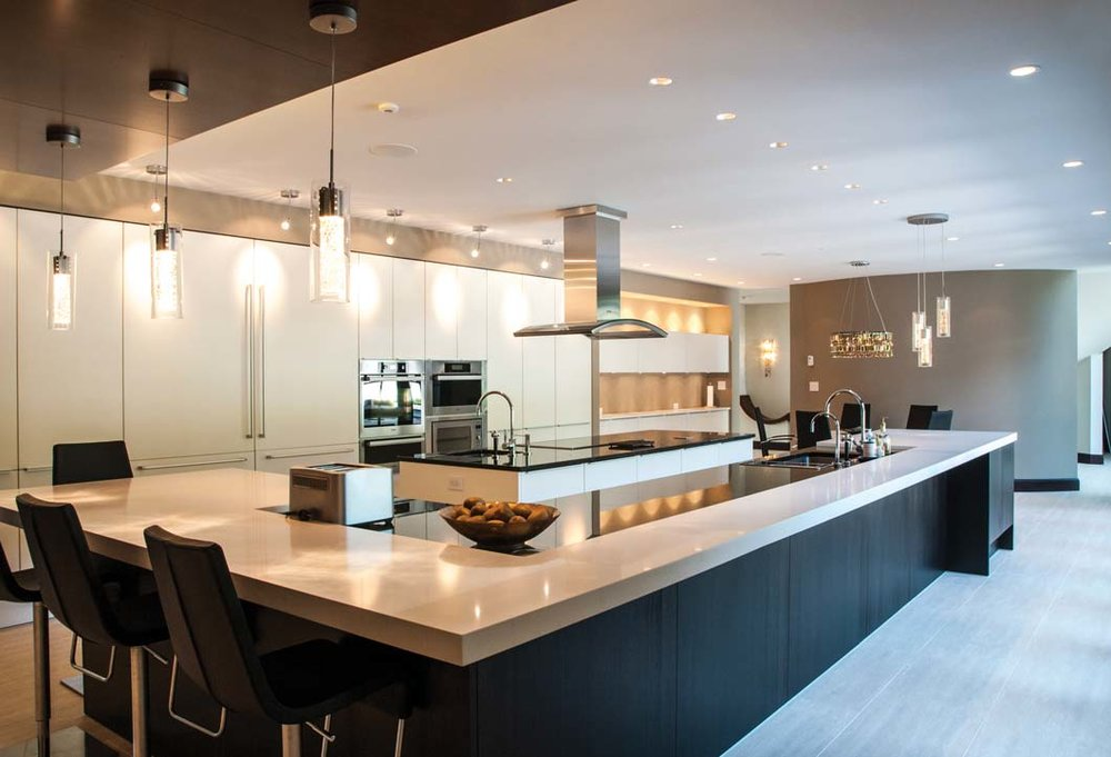 The Poggenpohl kitchen is designed with the connoisseur in mind. The clean, contemporary lines of this fully equipped kitchen merge effortlessly to facilitate practical efficiency. Contrasting dark granite wraps around light quartz countertops on two islands.