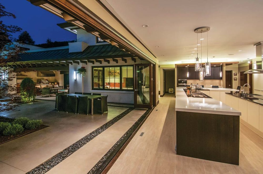 A 24-foot folding door opens fully from kitchen to patio and pool. The background reveals the kitchen coffee bar, family room, and covered outdoor kitchen. Gravel strips in the patio pick up driplines of the canopy roof.