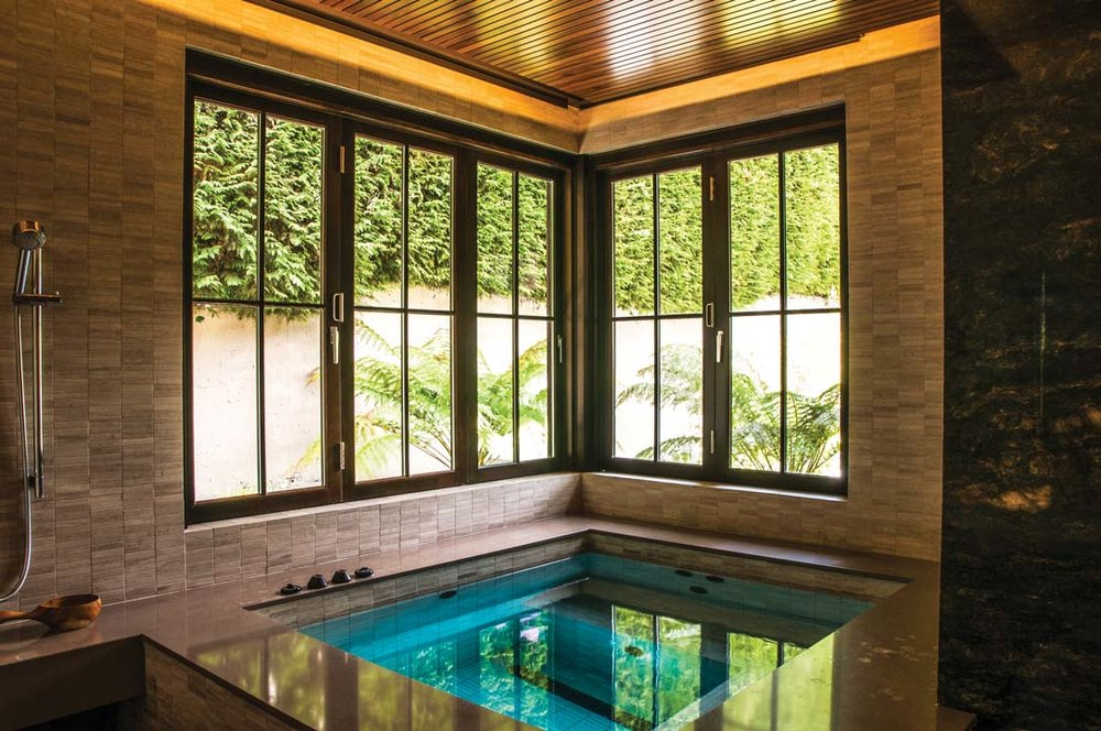 Under a unique dropped wood-slat ceiling, the spa hot tub overlooks the pool area through folding windows that open wide to the private garden.