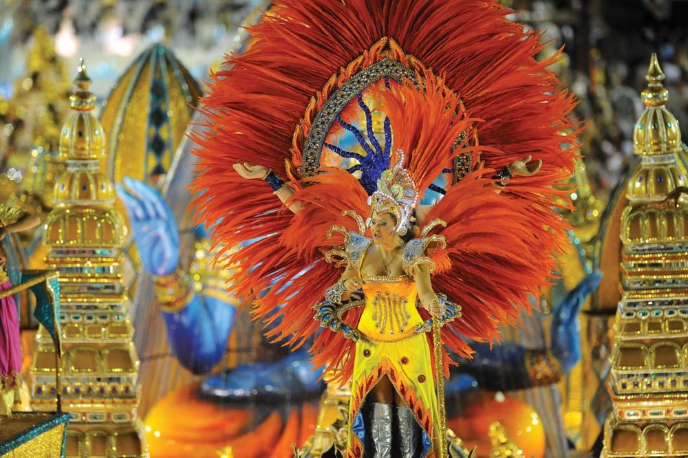 Samba dancers in elaborate costumes dance through the Sambadrome during carnival. CP DC Press / Shutterstock.com