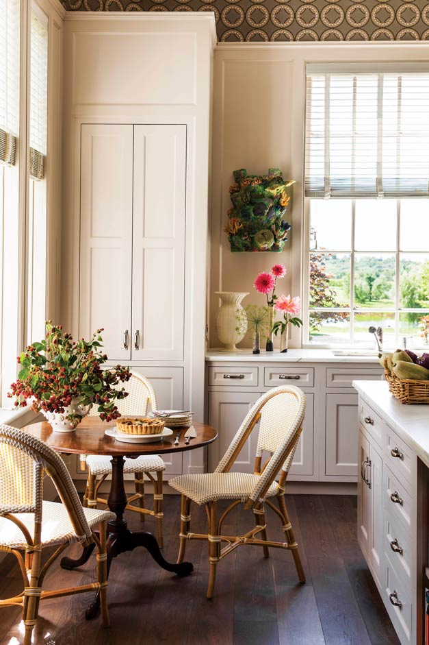 The simple elegance of the white kitchen is given vibrancy with dahlias from the cutting garden on the counter and aquatic decorations from the original Coney Island aquarium on the wall.