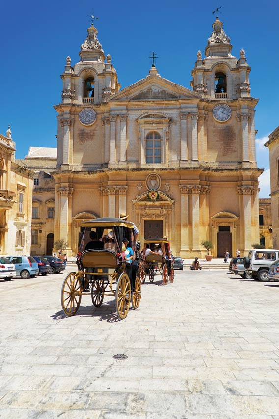 The tourist horse carriage on St Paul's Square in front of St Paul's Cathedral, Mdina, Malta. Serg Zastavkin / Shutterstock