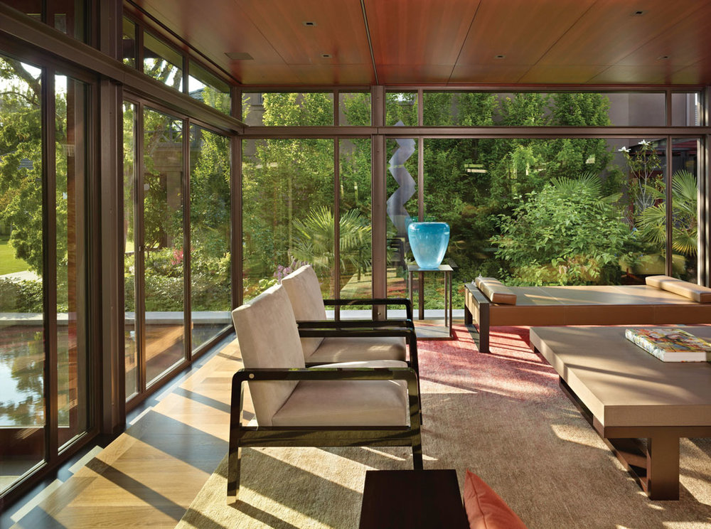 Under the lowered ceilings on either end of the Pavilion House are two living-room areas. This one is surrounded by glass, reflects outdoor light, and is next to a serene reflecting pool.