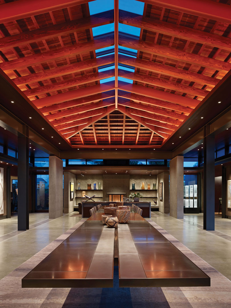 Under the ceiling is the 35-foot-long grand dining table by Garret Werner, interior designer, which sits on two pedestals. The table, which can seat 40 people, is constructed out of reclaimed  mahogany wood and nickel-plated steel sections. The lighting is designed by Brian Hook.