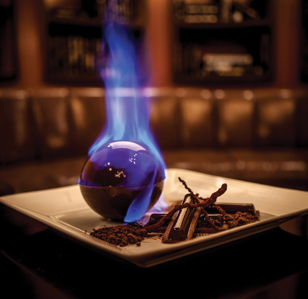 Fiery Salty Caramel Chocolate Tart — This sphere of dark chocolate sorbet, marshmallow, salty caramel ganache and spiced rum is set ablaze tableside, in a dramatic end to a Morimoto meal.