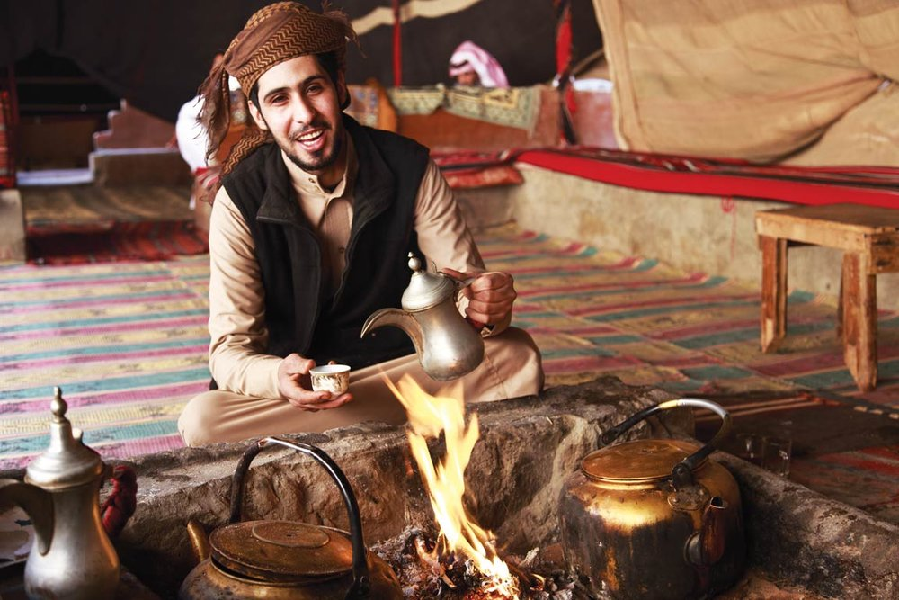 A Bedouin man makes coffee in the traditional style.  Ahmad A Atwah / Shutterstock.