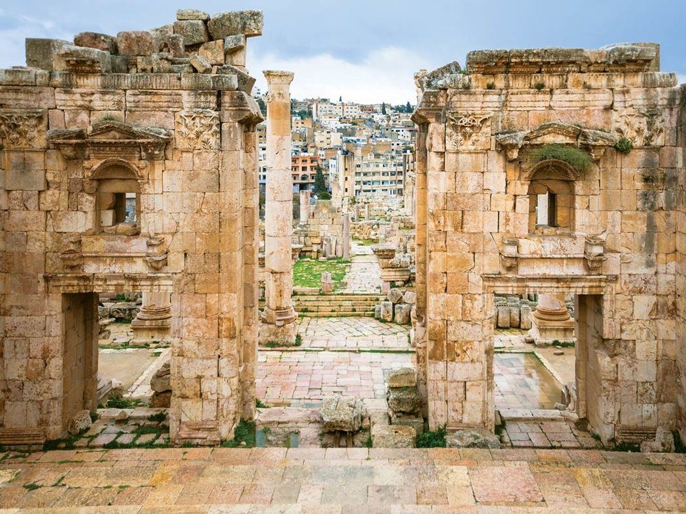 The modern city of Jerash can be seen through the Ancient Roman gateway of the Temple of Artemis.  vvoe / Shutterstock.com
