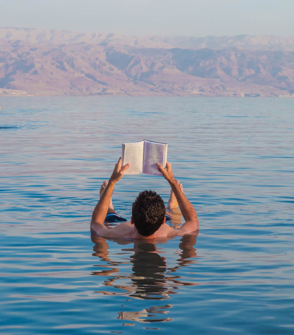 It's so easy to float in the Dead Sea, you can bring your favourite book; GuilhermeMesquita / Shutterstock.com