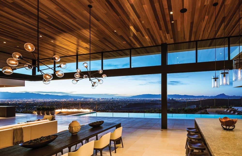 The view from the dining/entertainment area, of the rectangular pool that abuts the sunken fire pit. Looking beyond is a view of the western McCullough Range and Las Vegas.