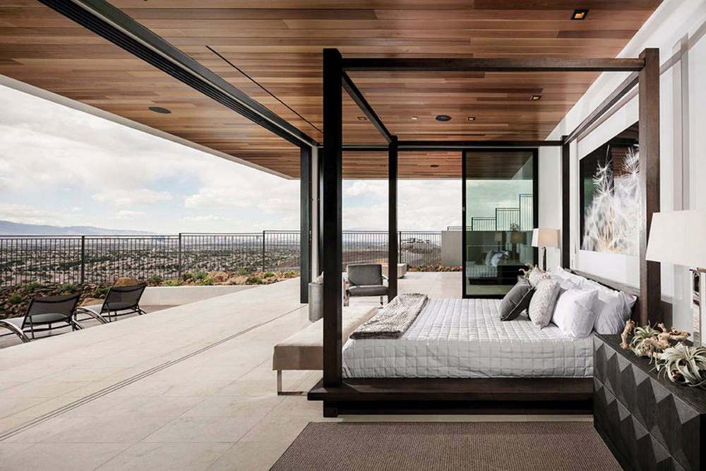 """Master bedroom, first floor, with """"disappearing"""" glass walls — this allows protection from desert weather, and on clear days, allows a perfect view of mountains and Las Vegas in the distance. The master bedroom has its own living room and direct access to the pool outside."""