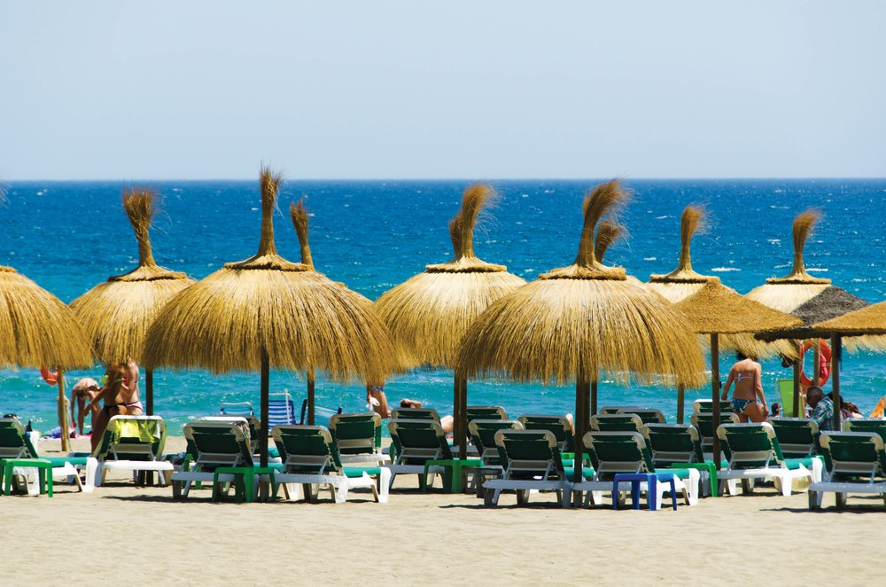 Straw umbrellas shade lounge chairs on a stretch of beach in Marbella.lisako66 / Shutterstock.com