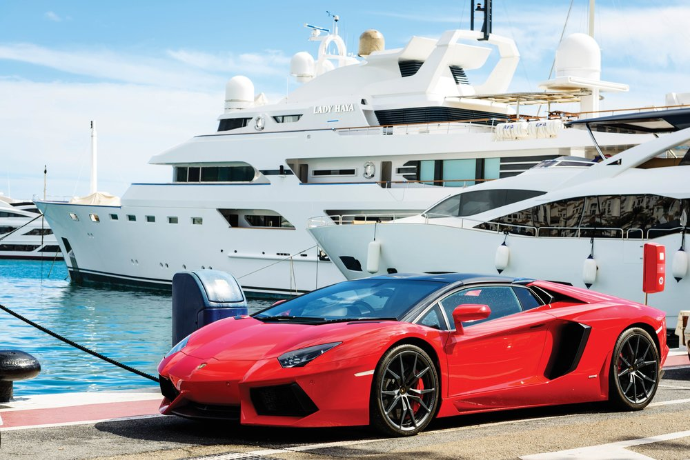 A Lamborghini in front of luxury yachts. Andres Garcia Martin / Shutterstock.com