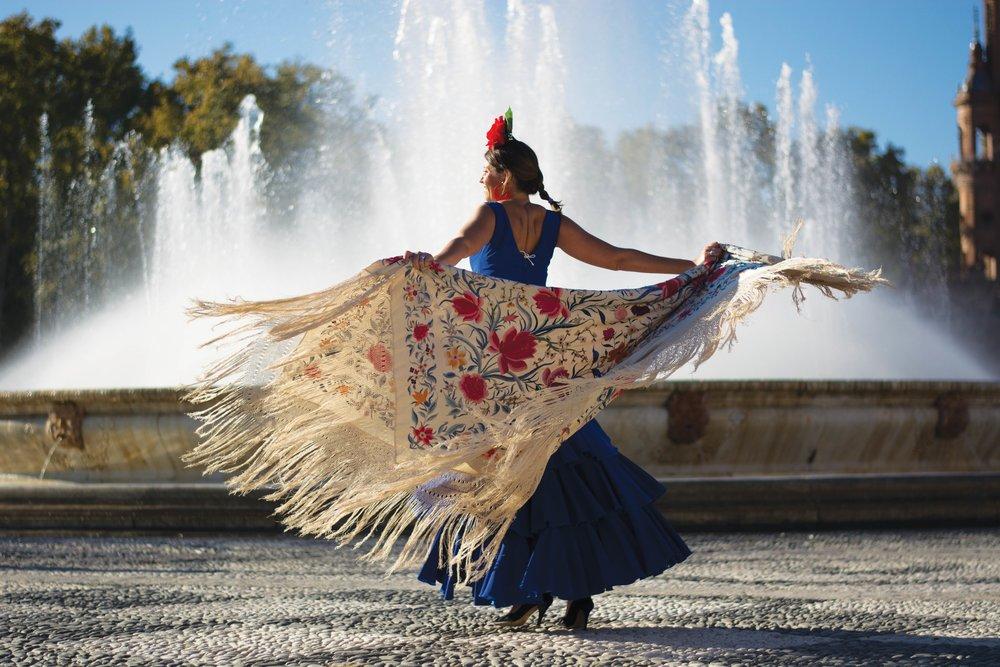 A flamenco dancer wears traditional dress and flowered mantle.Corrado/ Shutterstock.com;
