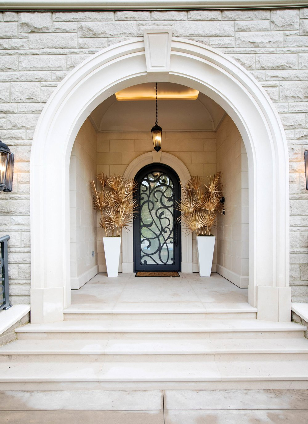 The front door begins the holiday welcome. A white entrance is accented by gold-dipped palm fronds. Courtesy of Granville Island Florist. T