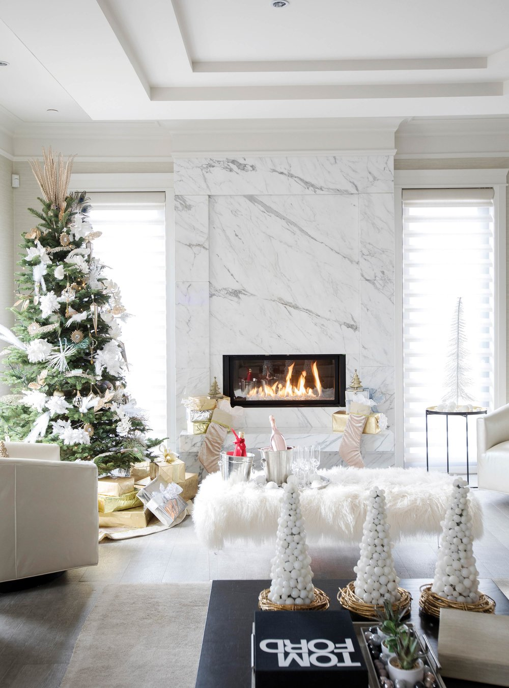 The colour palette of white and gold continues into a gathering area. Natural and manmade objects accent the area with gold, silver, and white ornaments, gift-wrapping, and accent lights on the tree.
