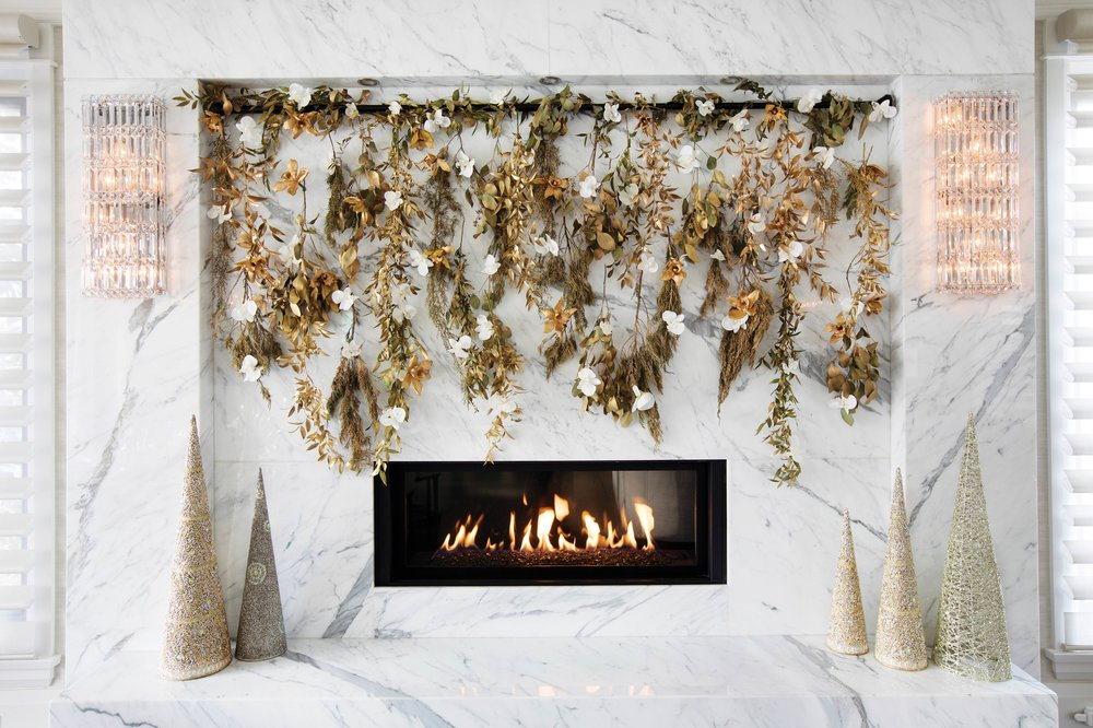 Vertical garlands embellish the white marble fireplace. These garlands combine local evergreens, gold-dipped Dendrobium orchids and leaves, along with white Phalaenopsis orchids. Courtesy of Granville Island Florist.
