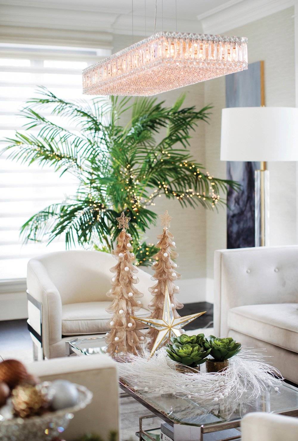 A memorable design surprise: a palm tree with small gold lights, completed by gold-dipped coffee-table décor with a white wreath surround. Courtesy of GardenWorks.
