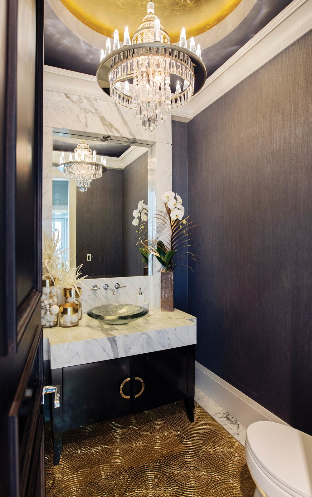 The powder room interior combines a grey marble bathroom vanity highlighted with white Christmas décor and a full blooming white Phalaenopsis orchid. Accenting the orchid is a single gold-dipped palm frond. Courtesy of Granville Island Florist.