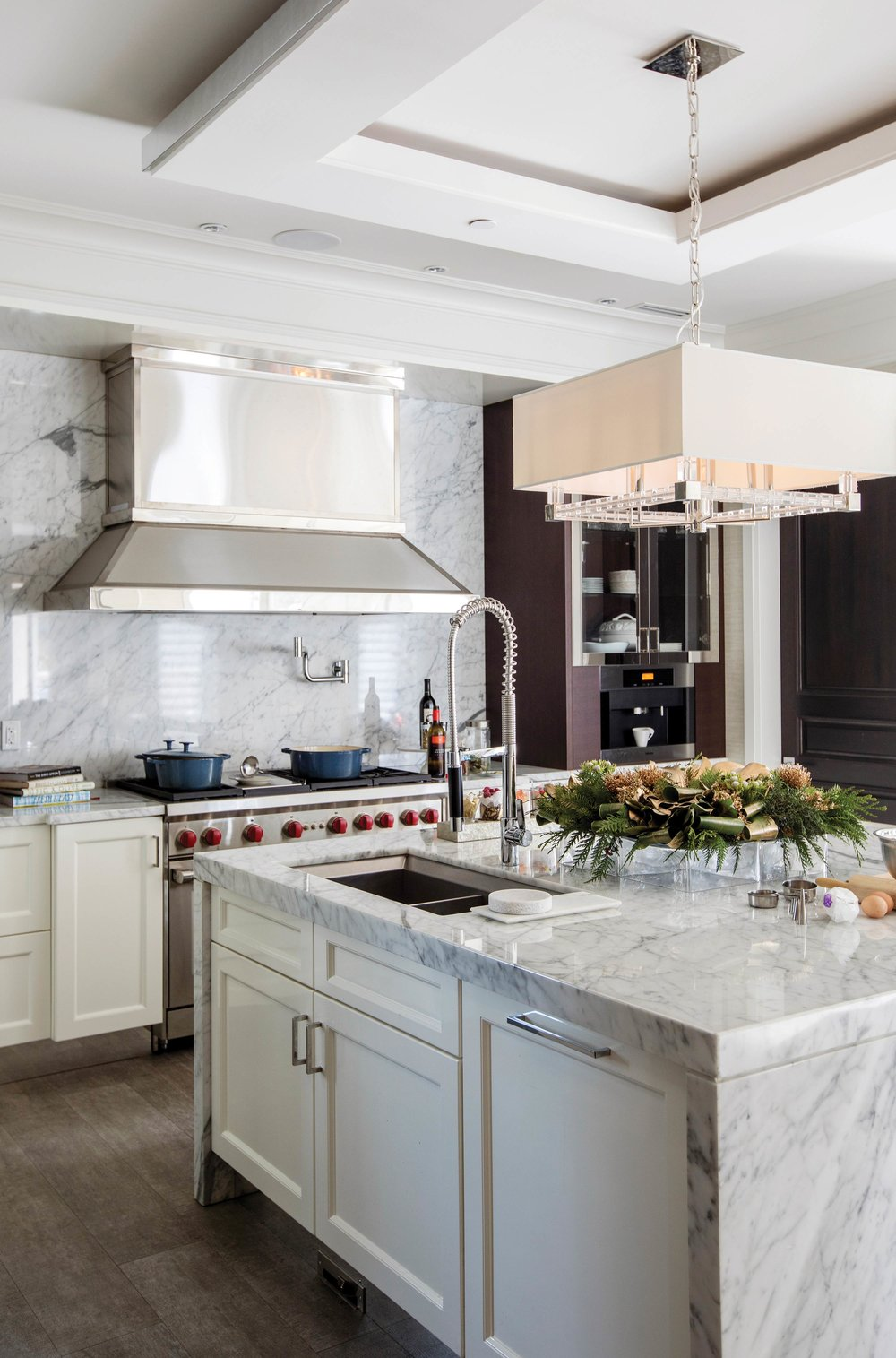 The white and grey marble kitchen interior is highlighted by a large kitchen island wreath, created from aromatic juniper and other evergreen leaves, dried Protea flowers, and wide-gold-ribbon accents. Courtesy of Granville Island Florist.