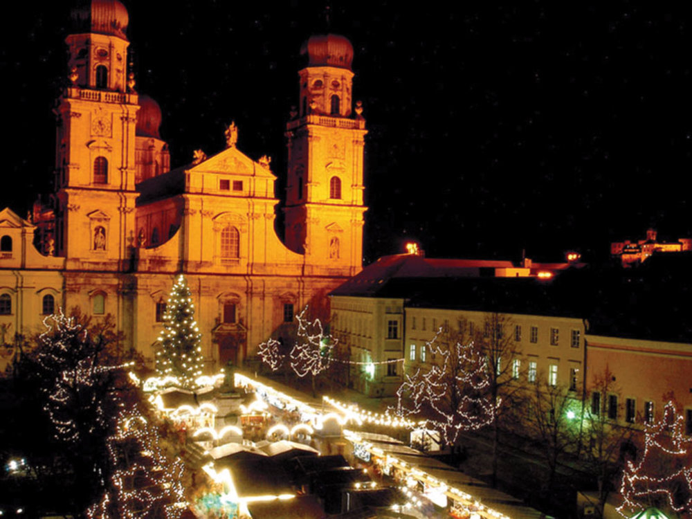St. Stephen's Church in Passau, with lighted vendor stalls and Christmas trees.Curioso/Shutterstock; T