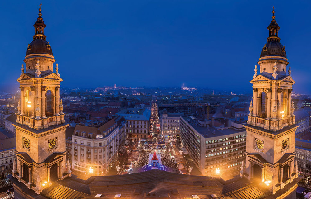The Vörösmarty Square Christmas Market in Budapest, with St. Stephen's Basilica spires rising in the foreground.Zoltan Gabor/Shutterstock.com;