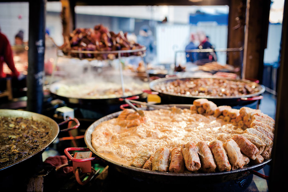 Christmas market delicacies: Kürtőskalács (chimney cake), along with Hurkas (grilled sausage) and Szaloncukor (parlor candy).Calin Stan/Shutterstock.com