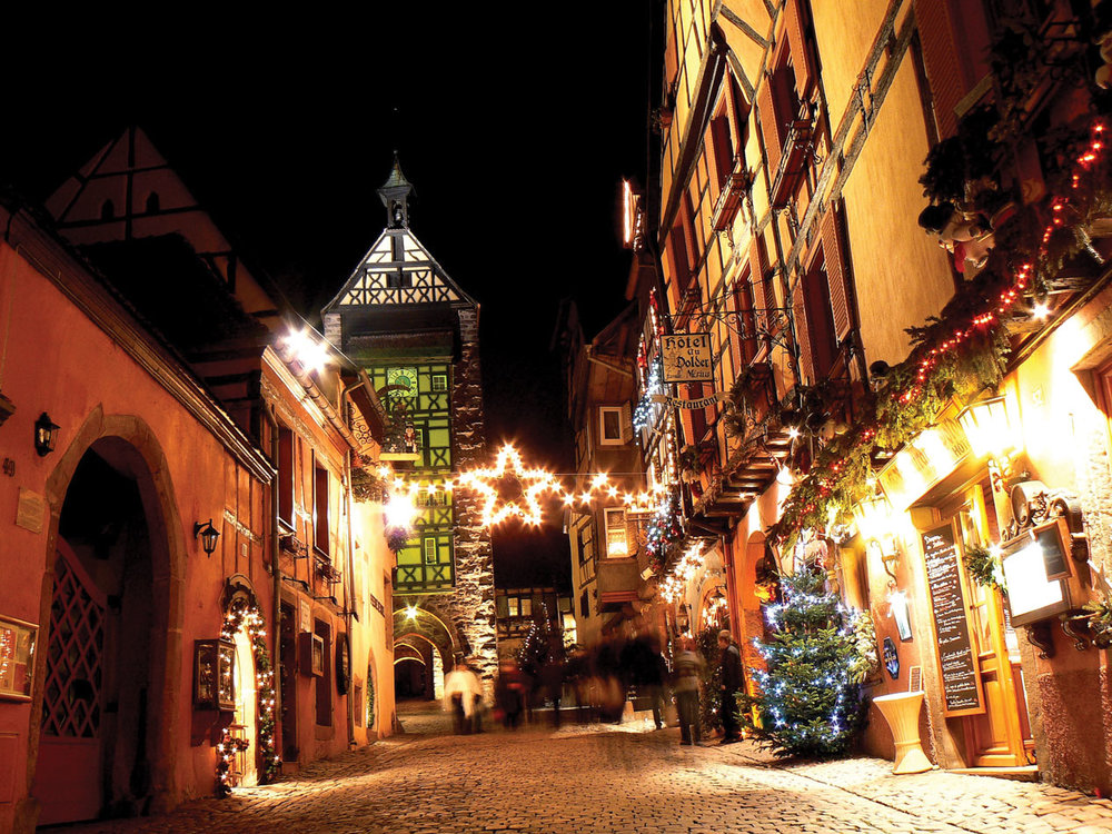 A Christmas-lighted cobblestone street in the medieval town of Riquewihr, leading to the Dolder Tower, the remaining part of a fortress built in the 13th century.Valery Bareta / Shutterstock.com