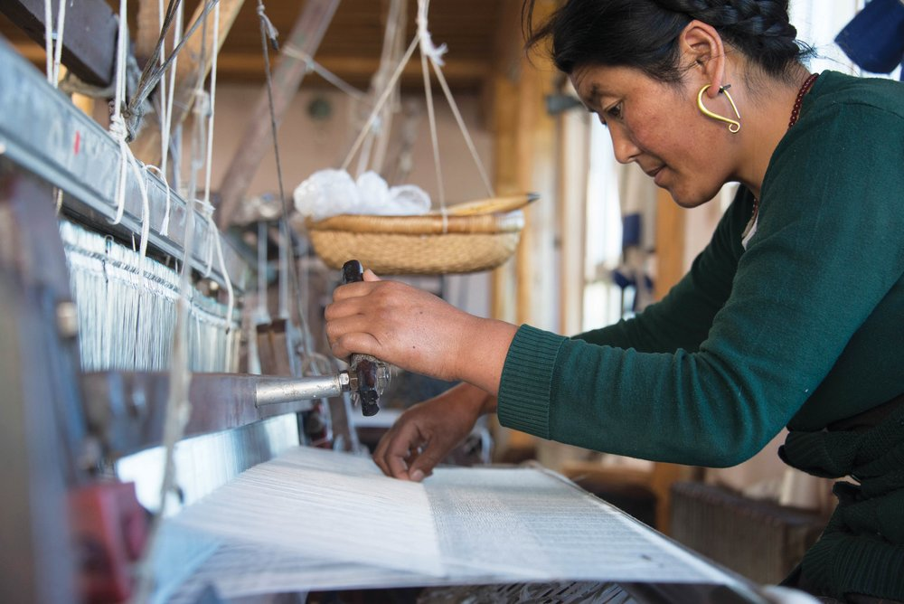At the atelier in Tibet, an artisan uses a loom to make a yak wool scarf.