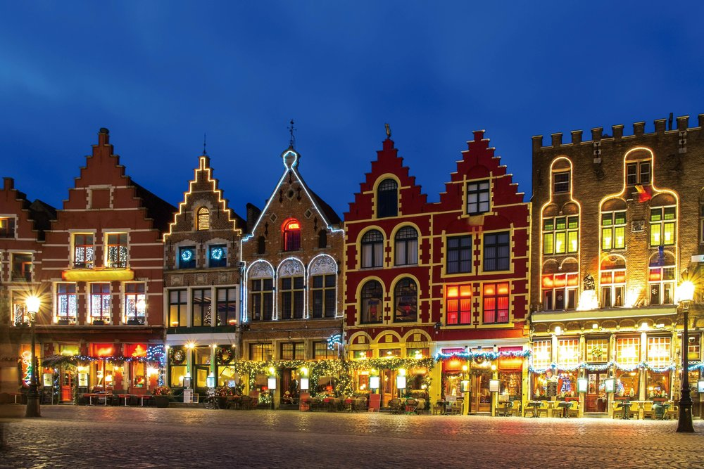 Market Square decorated for the Christmas holiday; Statue of Hans Memling.  Nejron Photo / Shutterstock.com
