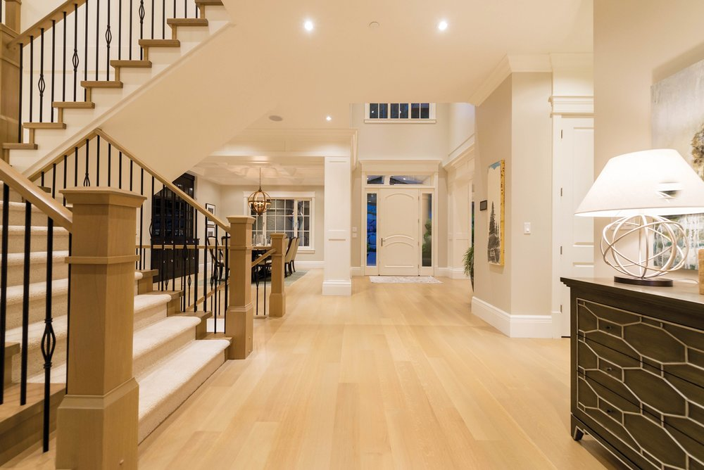 The foyer, entryway, and staircase are all finished with hues of natural-wood flooring, and are blended with a beige, white, and black colour palette. The hall and the stairway pillars reflect the classic form, which balances the colour schemes of the transitional design.
