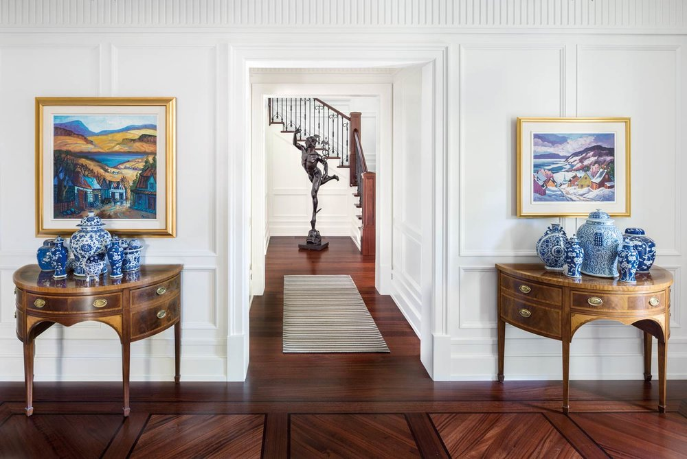 A full-sized bronze reproduction of Giambologna's Flying Mercury stands out in the formal entryway. Moving from the entryway, there is an eclectic collection of Chinese blue vases and urns on two matching demilune tables of the Italian Empire style. Above this collection are the clients' 20th-century Canadian paintings.