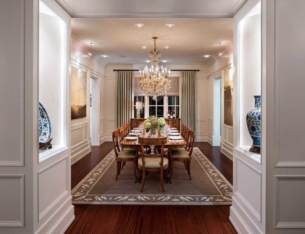 The dining room, with matching table and chairs set for ten, is of the Italian Empire style, as is the crystal chandelier. The draperies are wool.