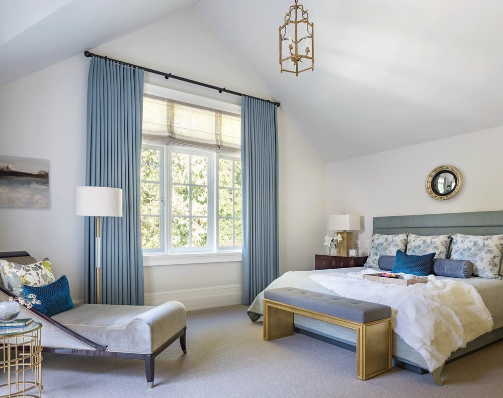 The master bedroom's drapes are lightweight wool, and the mirror above the bed is a round convex of the Regency style. The chaise on the left is from the Lucien Rollin collection in the French Moderne style, from William Switzer.