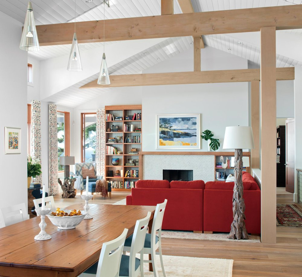 Cain harmonized heirloom pieces, such as the dinner table, with driftwood furniture, whites and blues, and even a rusty-red sofa for the perfect relaxing coastal mood. Photography by Barry Calhoun