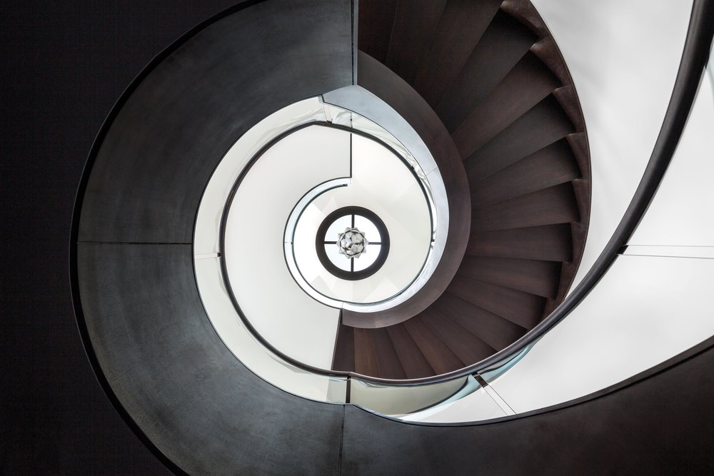 A helical staircase at the centre of the home ties the floors together, acting as a spiritual centre to the house. It starts in the basement and reaches up to a skylight. Constructed of steel, the stairs are covered in wood.