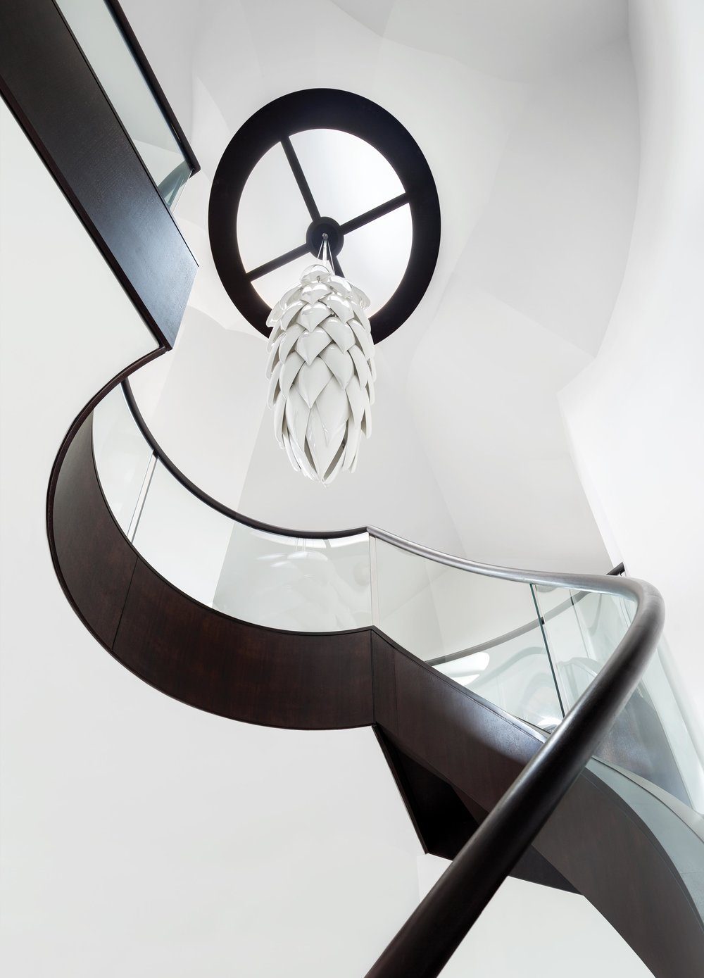 "A view of the main staircase from the ground floor, looking up at a ""fir-cone"" ceramic chandelier. The circular base of the ceramic hangs from a steel frame that straddles the skylight."