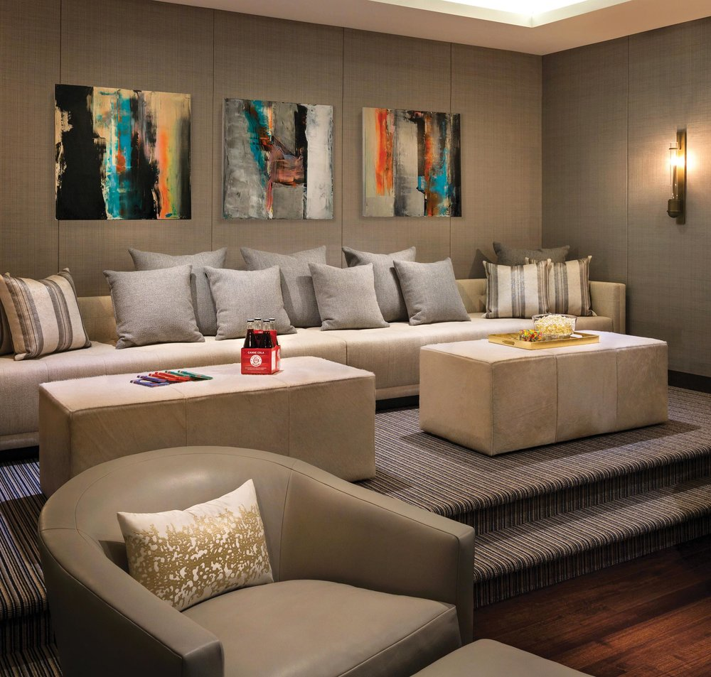 "Following the trend away from ""theatre"" style media rooms, the informal lounge-like atmosphere is created by introducing large sectionals and comfortable couches. Risers are used to ensure perfect screen viewing."