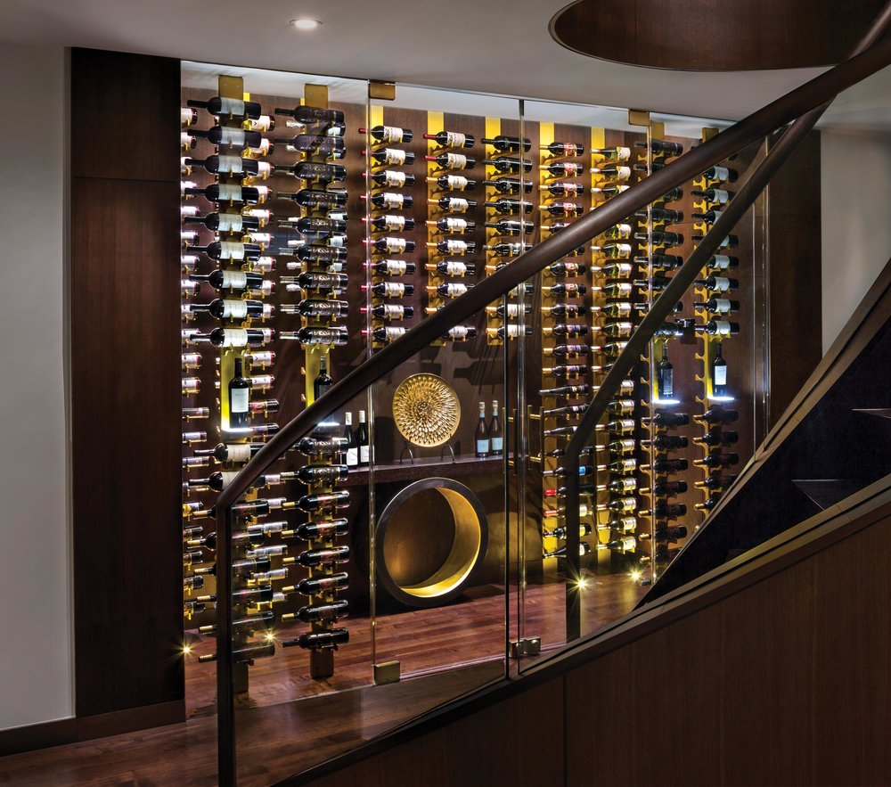 An advantage of mounting the wine bottles on horizontal racks is that their labels are visible for easy reading. The brass theme plays to the richness and polish of the wall-length, floor-to-ceiling cabinet.