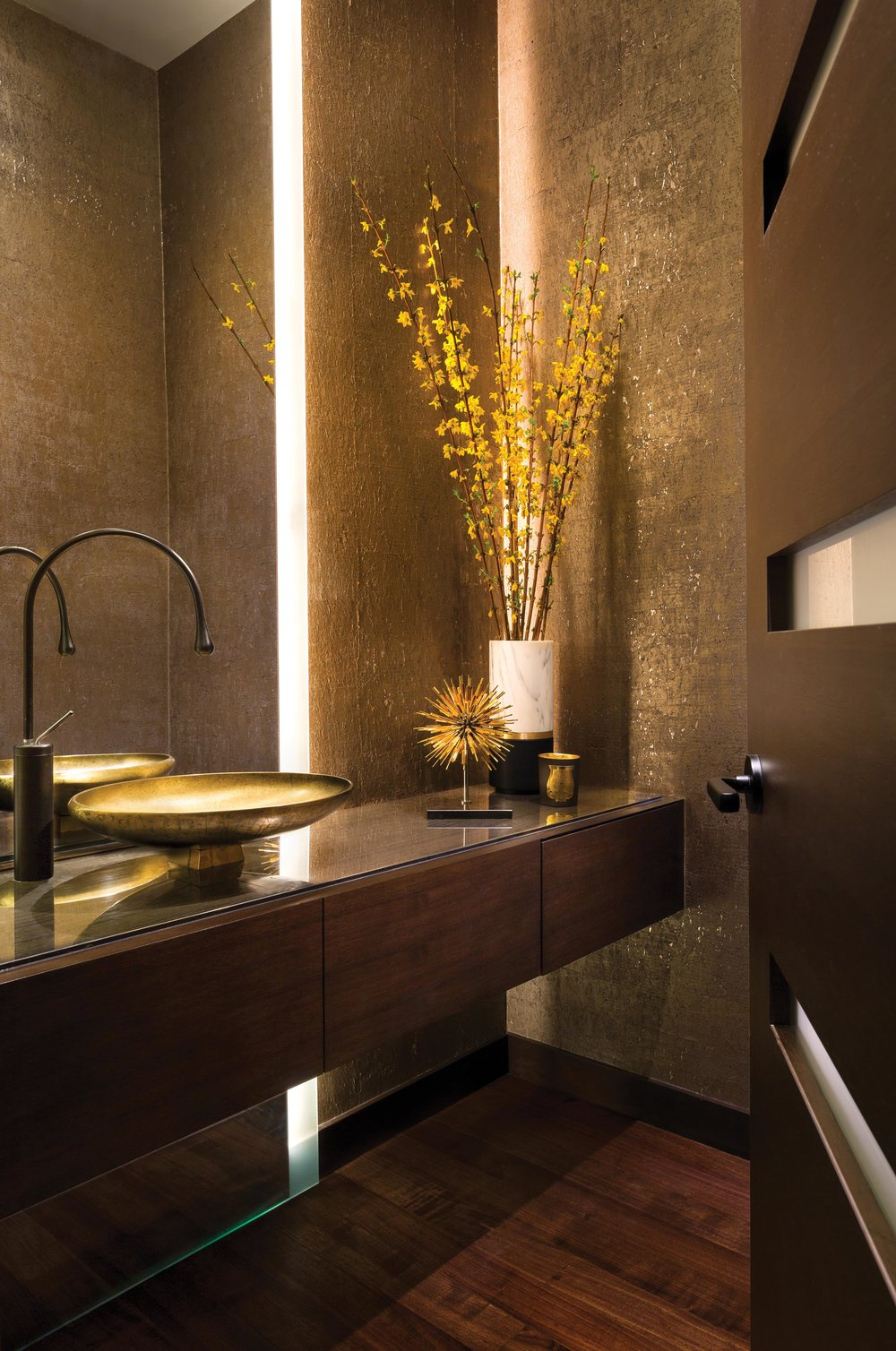 The warm ambience of the powder room is created with Smoke Screen marble by Aeon Stone & Tile, which sets off the bronze-finished sink and Gessi Goccia faucets.
