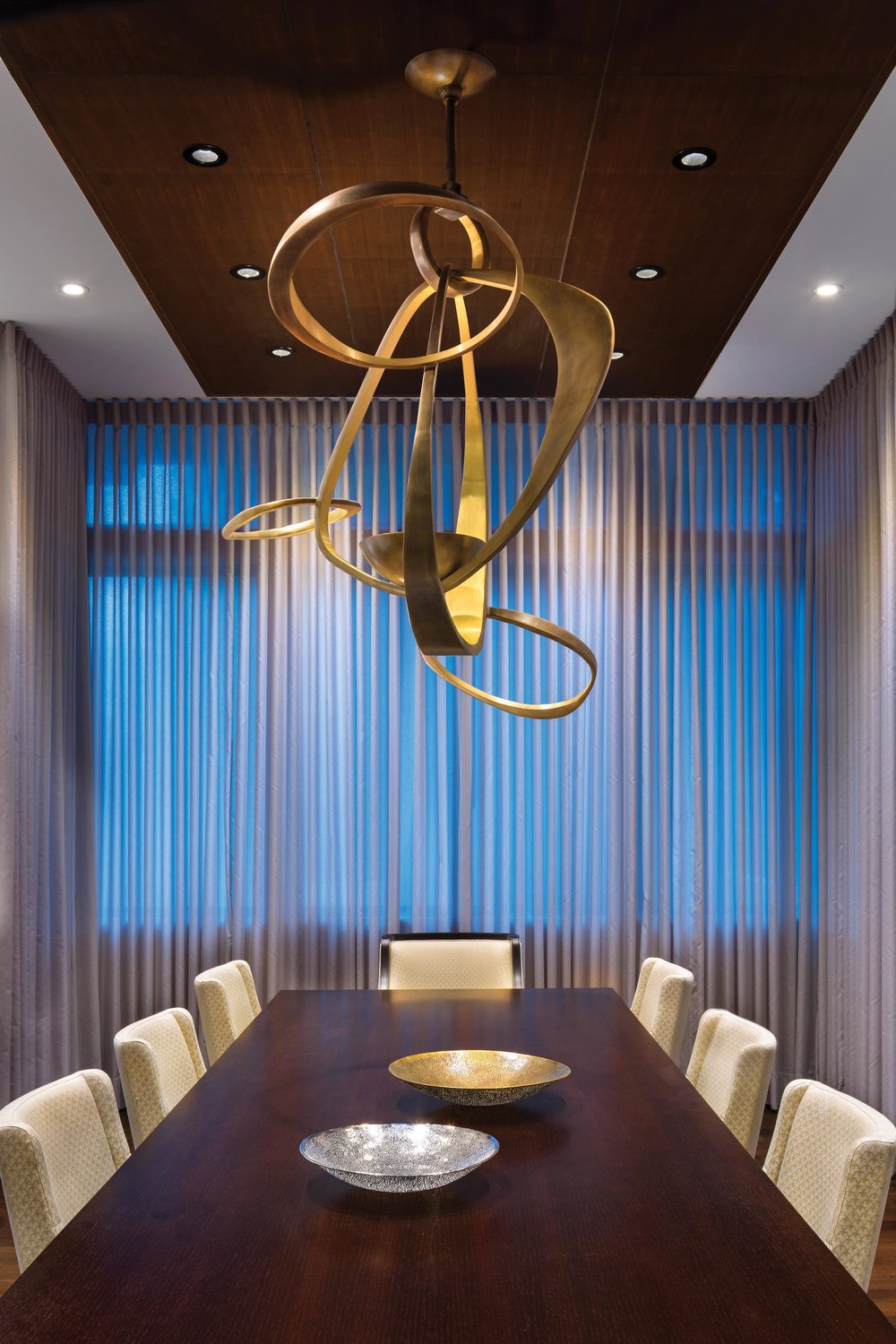 In the main dining room, a decorative walnut ceiling feature accentuates the axis while concealing the lighting alcoves and air vents. The chandelier centres the table and anchors the room, which is situated between the kitchen and living room without separating walls.