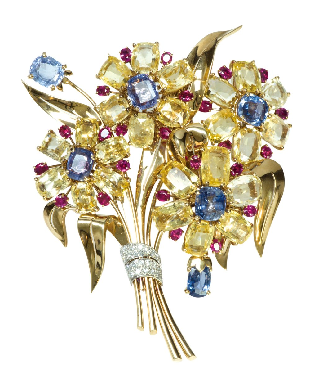 Trabert and Hoeffer Mauboussin Clip Brooch, circa 1950, featuring yellow gold and a multicolour floral spray with sapphire, ruby and diamond.  At DSF Antique Jewelry by appointment.  (929) 316-2746, dsfantiquejewelry.com