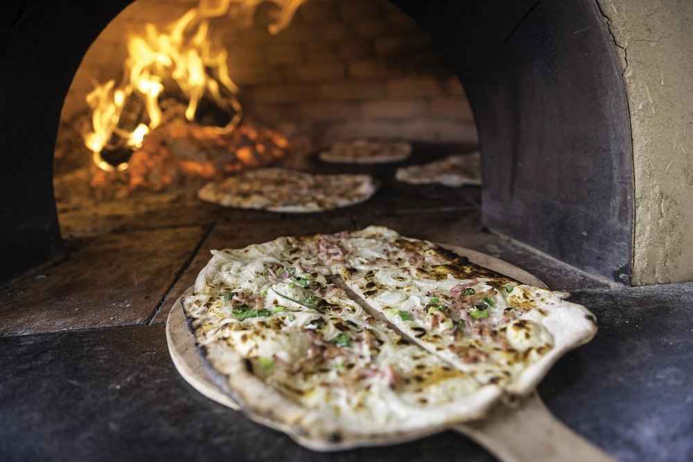 An uncooked tarte flambée Alsacienne, ready to bake in a wood-fired oven.By Gyuszko-Photo / Shutterstock.com