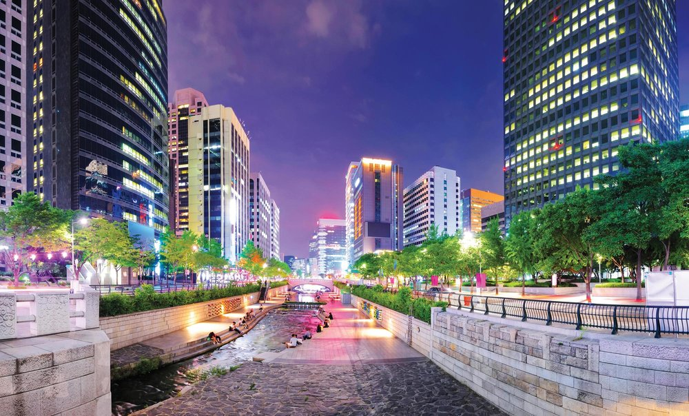 Locals flank the river of Cheonggyecheon Park at night. Apple_Foto / Shutterstock.com