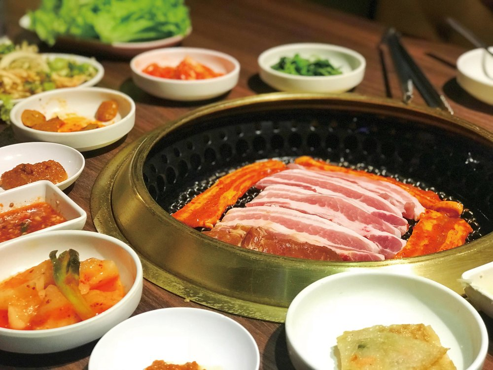 Traditional Korean tabletop grill and banchan dishes. Dekcos/ Shutterstock.com