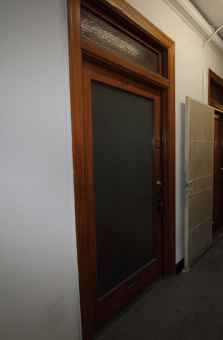 Original 1925 office door with transom, before rehabilitation.
