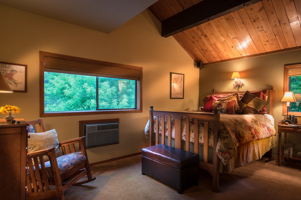 The Harvest - Views of the forest and meadow are enjoyed in this antique raised queen bed with vaulted ceiling.