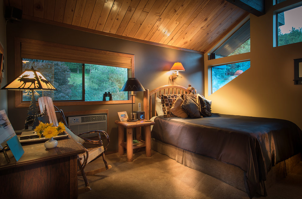 The Moose - Views of the forest and meadow are enjoyed from the many windows in this corner room with vaulted ceiling.