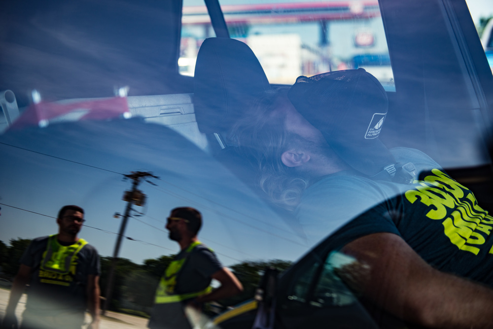 Crew member Ryan Jean sleeps in one of the follow vehicles as crew members Tyler Jandreau and Joseph Joseph wait for Marshall to arrive for a quick stop on June 21st, 2016. Marshall's crew consisted of only 6 people who had to alternate shifts while Marshall was on the bike for more than 20 hours a day.