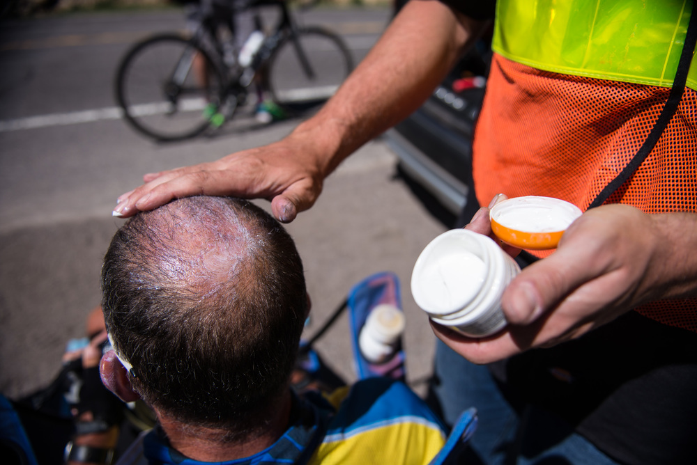 Crew member Tyler Jandreau applies zinc oxide cream to Marshall's head to prevent sunburns during the day ride on June 18th, 2016.